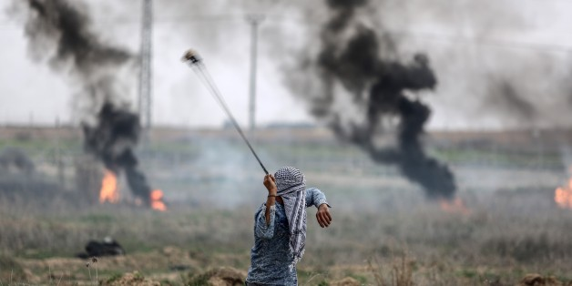 GAZA CITY, GAZA - DECEMBER 22 : A Palestinian protester uses slingshot to throw at Israeli security forces during a demonstration against U.S. President Donald Trump's recognition of Jerusalem as Israel's capital, at Israeli border in Shuja'iyya neighborhood of Gaza City, Gaza on December 22, 2017. (Photo by Ali Jadallah/Anadolu Agency/Getty Images)