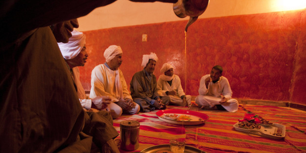 Dates and sweet tea being served to visitors in Bamhar village, some 40 km south of Adrar. The town is supplied with irrigation water by an ancient and well-maintained network of 'foggara' or subterranean aqueducts. The young people are not interested in the hard work of maintaining the foggara, so the work rests with this group of old men seen here.