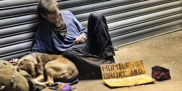 New York, USA - May 16, 2013: homeless man sleeping with dog on sidewalk on 8th Ave and 42th Street, Manhattan, NY.