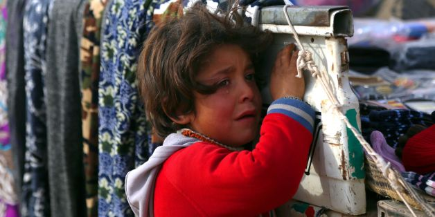 A displaced Syrian child, who was forced to leave his hometown by the war against the Islamic State (IS) group, is seen at the Ain Issa camp on December 18, 2017.    As temperatures drop, tens of thousands of civilians forced out of their homes by Syria's war are spending yet another winter in flimsy plastic tents or abandoned half-finished buildings. And without heating, blankets and warm clothes, or access to proper medical care, even a simple cold can turn deadly. / AFP PHOTO / Delil souleima