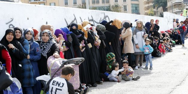Syrian refugees queue to receive aid consisting of winter clothing, blankets, heaters and other necessities, in the capital Beirut's Martyrs Square on November 26, 2017, as part of the 'Dafa' campaign aimed at helping Syrian refugees and Lebanese families in need. / AFP PHOTO / ANWAR AMRO        (Photo credit should read ANWAR AMRO/AFP/Getty Images)