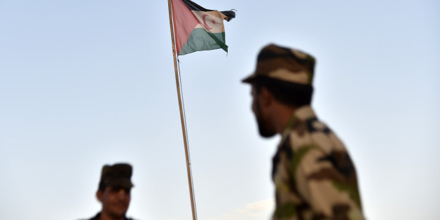 Uniformed soldiers of the pro-independence Polisario Front stand before a Sahrawi flag flying at the Boujdour refugee camp near the town of Tindouf in Western Algeria on October 17, 2017. / AFP PHOTO / RYAD KRAMDI / RYAD KRAMDI / The erroneous mention[s] appearing in the metadata of this photo by RYAD KRAMDI has been modified in AFP systems in the following manner: 'near the town of Tindouf in Algeria' instead of 'in the disputed territory of Western Sahara'. Please immediately remove the erroneous mention from all your online services and delete it  from your servers. If you have been authorized by AFP to distribute it to third parties, please ensure that the same actions are carried out by them. Failure to promptly comply with these instructions will entail liability on your part for any continued or post notification usage. Therefore we thank you very much for all your attention and prompt action. We are sorry for the inconvenience this notification may cause and remain at your disposal for any further information you may require.        (Photo credit should read RYAD KRAMDI/AFP/Getty Images)