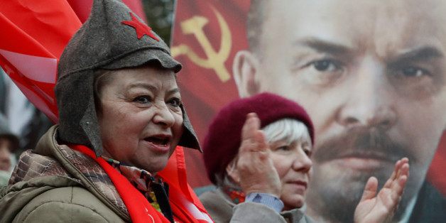 Demonstrators react in front of a portrait of Soviet state founder Vladimir Lenin during a rally held by Russian Communist party to mark the Red October revolution's centenary in central Moscow, Russia November 7, 2017. REUTERS/Sergei Karpukhin