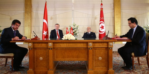 TUNIS, TUNISIA - DECEMBER 27: Turkish Economy Minister Nihat Zeybekci (L) and his Tunisian counterpart sign a bilateral agreement as they are flanked by President of Turkey Recep Tayyip Erdogan (2nd L) and Tunisian President Beji Caid Essebsi (2nd R) in Tunis, Tunisia on December 27, 2017.  (Photo by Kayhan Ozer/Anadolu Agency/Getty Images)