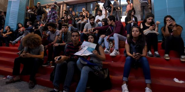 Tunisian youths check the programme as they wait outside a movie theatre during the Carthage Film Festival in Tunis' seaside suburb of Carthage on November 2, 2016.The Carthage film festival will run from from October 28 to November 5.  / AFP / FETHI BELAID        (Photo credit should read FETHI BELAID/AFP/Getty Images)