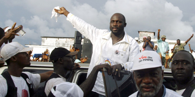 "Liberian presidential candidate and former world footballer of the year George Weah (C) arrives for an address to supporters in Monrovia November 6, 2005. Weah will face a presidential run-off on Tuesday against Ellen Johnson-Sirleaf, a former finance minister known as the ""Iron Lady"". Liberians hope a second-round presidential run-off can heal the wounds left by a brutal civil war. Picture taken November 6, 2005. REUTERS/Tim Hetherington"