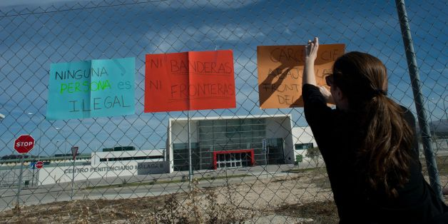 A woman hangs placards reading 'Nobody is illegal' and 'No flags no borders' outside the new and yet to open jail of Archidona, on November 26, 2017, where nearly 500 migrants who arrived in the country by boat last week are held.The Spanish government said that the migrants are held in Archidona´s jail due to a lack of space at immigration detention centres. Migrants who arrive in Spain by boat are usually initially detained in police facilities for identification and processing before being