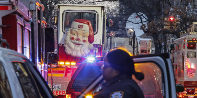 A Santa Claus figure is seen on the door of a fire truck as a New York Police Department (NYPD) officer works on the scene of an apartment fire on December 29, 2017 in the Bronx borough of New York City.Officials said Friday that the death toll from the fire has reached 12, including four children. / AFP PHOTO / KENA BETANCUR        (Photo credit should read KENA BETANCUR/AFP/Getty Images)