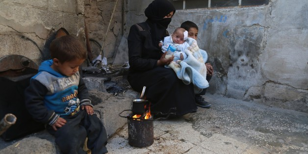 DAMASCUS, SYRIA - DECEMBER 28: A woman holds Syrian baby Karim, who lost his left eye and his mother after Assad regime's attack on Hammuriye district, in besieged Damascus suburb of Eastern Ghouta, Syria on December 28, 2017. Baby Karim is at risk of losing his right eye as well. (Photo by Amer Alshami/Anadolu Agency/Getty Images)