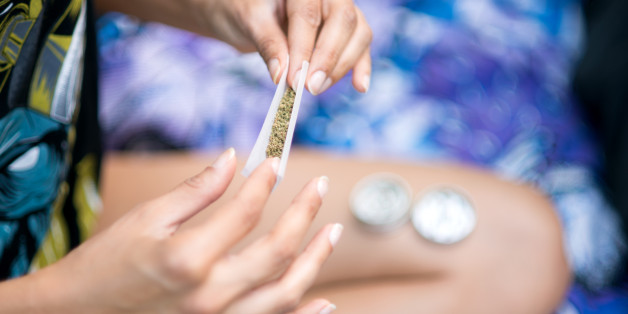 Close up of a woman rolling joint at the park