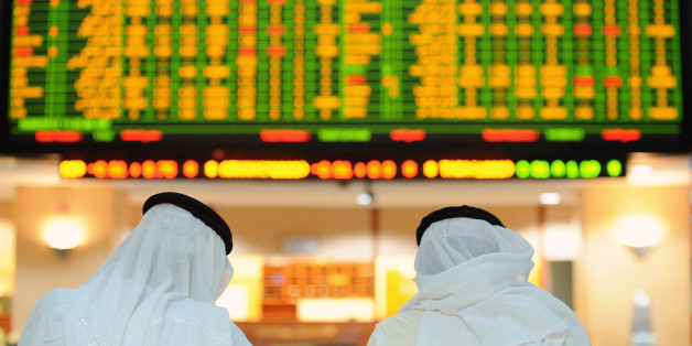 Investors look up at electronic boards displaying stock information at the ADX Abu Dhabi Securities Exchange stock market May 16, 2012. REUTERS/Ben Job (UNITED ARAB EMIRATES - Tags: BUSINESS)