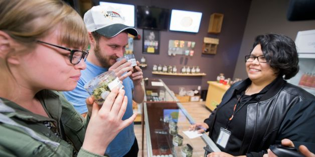 Tourists Laura Torgerson and Ryan Sheehan, visiting from Arizona, smell cannabis buds at the Green Pearl Organics dispensary on the first day of legal recreational marijuana sales in California, January 1, 2018 in Desert Hot Springs, California. / AFP PHOTO / Robyn Beck        (Photo credit should read ROBYN BECK/AFP/Getty Images)