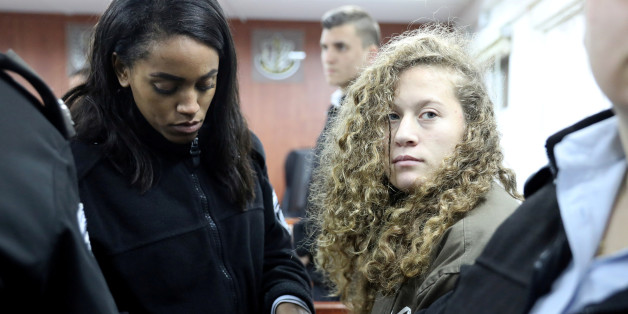 Palestinian teen Ahed Tamimi (R) enters a military courtroom escorted by Israeli Prison Service personnel at Ofer Prison, near the West Bank city of Ramallah, January 1, 2018. REUTERS/Ammar Awad     TPX IMAGES OF THE DAY