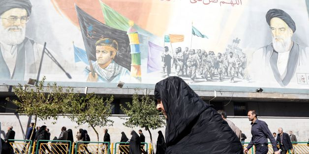 An Iranian woman walks past pictures of Iranian supreme leader Ayatollah Ali Khamenei (top L) and of late Iranian supreme leader Ayatollah Ruhollah Khomeini (top R), following the weekly Friday prayer in Tehran on October 13, 2017.President Donald Trump will unveil a more aggressive strategy to check Iran's growing power, but will stop short of withdrawing from a landmark nuclear deal or declaring the powerful Islamic Revolutionary Guard Corps a terrorist organization. During a White House speec