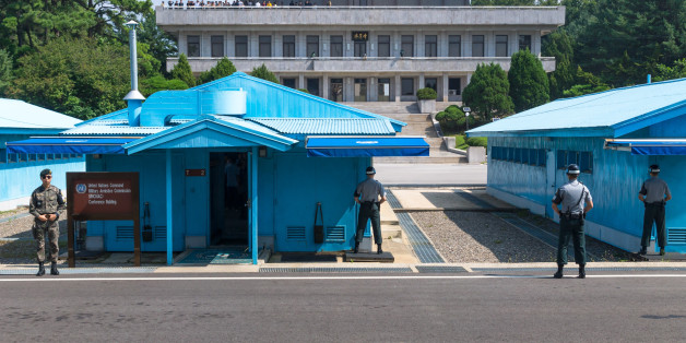 Jsa Within Dmz: UN soldiers close in front of blue buildings at North South Korean border with North Korean tourists in the background at Korean Demilitarized Zone, Panmunjom