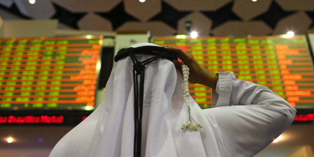 A visitor holds prayer beads while looking at financial information screens at the Dubai Financial Market (DFM) in Dubai, United Arab Emirates, on Tuesday, Nov. 10, 2015. Dubai's index declined for three straight months after a collapse in the price of crude battered economies in the oil-producing nations of the Gulf Cooperation Council. Photographer: Jasper Juinen/Bloomberg via Getty Images