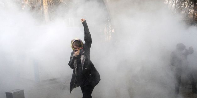 TOPSHOT - An Iranian woman raises her fist amid the smoke of tear gas at the University of Tehran during a protest driven by anger over economic problems, in the capital Tehran on December 30, 2017.Students protested in a third day of demonstrations sparked by anger over Iran's economic problems, videos on social media showed, but were outnumbered by counter-demonstrators. / AFP PHOTO / STR        (Photo credit should read STR/AFP/Getty Images)