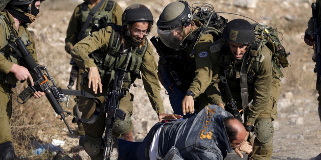 Israeli soldiers detain a Palestinian protester during clashes following a protest against Jewish settlements, in Jalazoun refugee camp, near the West Bank city of Ramallah June 12, 2015. REUTERS/Mohamad Torokman      TPX IMAGES OF THE DAY           TPX IMAGES OF THE DAY