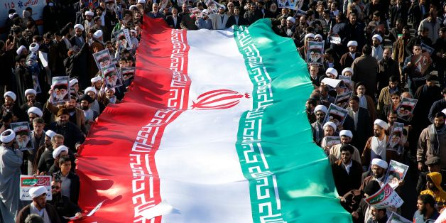 Pro-government demonstrators wave their national flag during a march in Iran's holy city of Qom, some 130 kilometres south of Tehran, on January 3, 2018, as tens of thousands gathered across Iran in a massive show of strength for the Islamic rulers after days of deadly unrest. / AFP PHOTO / Mohammad ALI MARIZAD        (Photo credit should read MOHAMMAD ALI MARIZAD/AFP/Getty Images)