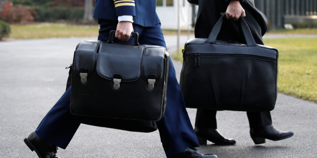 "A military aide carries the so-called ""nuclear football,"" which contains launch codes for the U.S. nuclear arsenal and which travels with the sitting U.S. president, to depart with U.S. President Donald Trump for travel to Utah from the White House in Washington, U.S. December 4, 2017.  REUTERS/Jonathan Ernst"