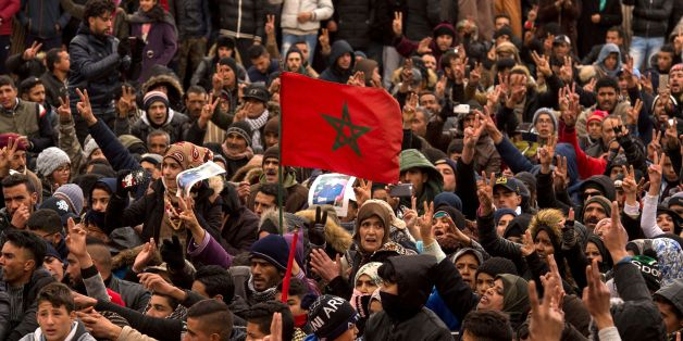 Moroccans shout slogans and wave their national flag as they participate in a demonstration after the funeral of two brothers who died while digging in an abandoned coal mine in the northeastern city of Jerada, 60 kilometres southwest of Oujda, on December 27, 2017. 