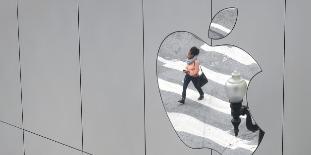 A woman is reflected in a Apple store logo in San Francisco, California, U.S., August 21, 2017.   REUTERS/Kevin Coombs