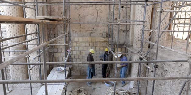In this photograph taken on November 8, 2017 shows Afghan labourers working amidst scaffolding for the ongoing conservation work at the ninth-century mosque Masjid-e Haji Piyada (mosque of the walking pilgrim) in Balkh Province.In the white dusty plains of northern Afghanistan, archeologists and conservationists are seeking to unravel the secrets of an one of the oldest mosques in the world, whose structure is still standing after a thousand years of solitude. / AFP PHOTO / FARSHAD USYAN / To go