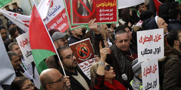 Palestinian protesters hold placards as the convoy of Jerusalem's Greek Orthodox patriarch Theophilos III arrives in the West Bank town of Bethlehem on January 6, 2018 ahead of a Christmas service according to the Eastern Orthodox calendar. The municipalities of Bethlehem, Beit Sahour and Beit Jala, all in the Israeli-occupied West Bank, called for the boycott over Jerusalem's Greek Orthodox patriarch allegedly allowing controversial real estate sales.  / AFP PHOTO / Musa AL SHAER        (Photo