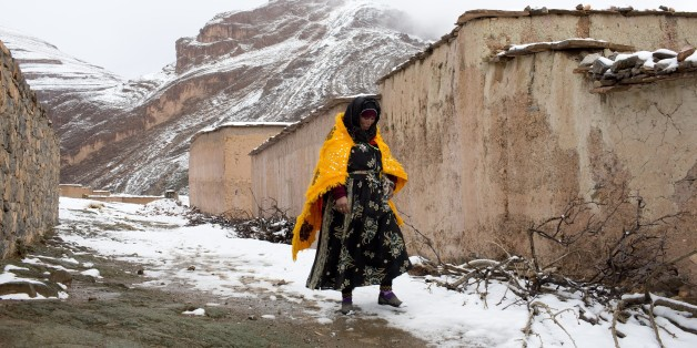 A woman walks through the snow covered village of Tilmi in the High Atlas region of Morocco February 13, 2015. The snowy foothills of the High Atlas mountains in Morocco are home to several Berber villages where the inhabitants make their living by farming, baking bread in traditional ovens, herding cattle, and the making and selling of honey, olive oil and pottery. Extreme weather fluctuations and erosion that causes flooding and landslides have led to a drop in agricultural productivity, the U