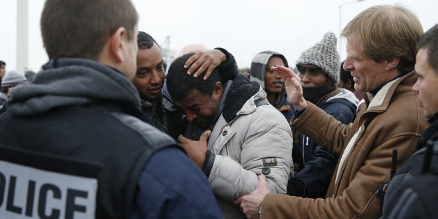 """Pascal Brice (R), the head of OFPRA, French Office for Refugees and Stateless Persons, comforts an Ethiopian migrant, member of the Oromo community, who cries as he leaves the """"Jungle"""" to be transfered to reception centers during the start of the dismantlement of the camp in Calais, France, October 24, 2016.   REUTERS/Pascal Rossignol"""