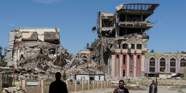 "People walk in front of the remains of the University of Mosul, which was burned and destroyed during a battle with Islamic State militants, in Mosul, Iraq, April 10, 2017. Marko Djurica: ""On April 10, a Reuters team entered eastern Mosul to work on a story about the the city's destroyed university, once a centre for education in northern Iraq. On arrival, I was struck first by the huge size of the campus, then by the scale of destruction. At least 10 large buildings and some smaller ones had be"