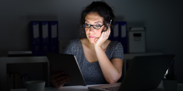 Woman in an office, using computer and working at night.