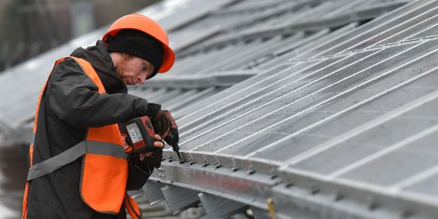 A worker installs photovoltaic panels on the new one-megawatt power plant next to the New Safe Confinement over the fourth block of the Chernobyl nuclear plant on December 12, 2017.At ground zero of Ukraine's Chernobyl tragedy, workers in orange vests are busy erecting hundreds of dark-coloured panels as the country gets ready to launch its first solar plant to revive the abandoned territory. The new one-megawatt power plant is located just a hundred metres from the new 'sarcophagus', a giant me