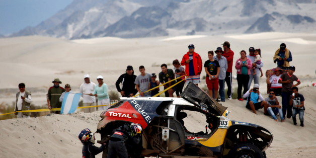Carlos Sainz (L) of Spain and co-pilot Lucas Cruz work on a tire of their Peugeot during the 10th stage of the Dakar Rally 2016 near Fiambala, Argentina, January 13, 2016.  REUTERS/Marcos Brindicci