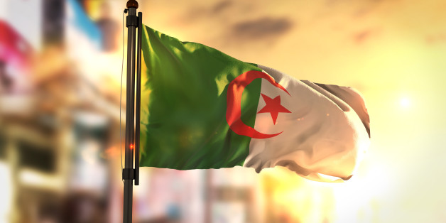 Algeria Flag Against City Blurred Background At Sunrise Backlight