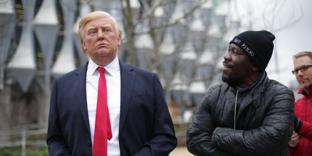 A man stands next to the Madame Tussauds wax figure of US President Donald Trump outside the new US Embassy in Nine Elms, London, after Mr Trump confirmed he will not travel to the UK to open the new building - and hit out at the location of the 1.2 billion dollar (£886 million) project. (Photo by Yui Mok/PA Images via Getty Images)