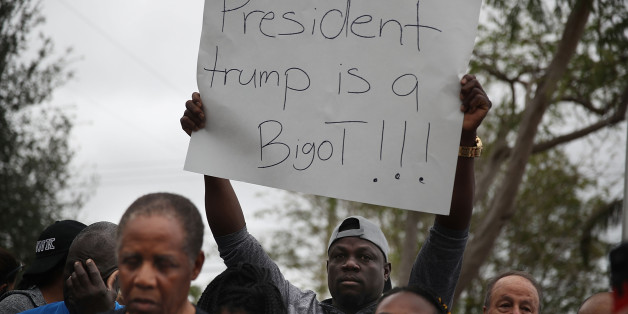 MIAMI, FL - JANUARY 12: Jorel Francois holds a sign that reads, 'President trump is a Bigot!!!' as he joins with others to mark the 8th anniversary of the massive earthquake in Haiti and to condemn President Donald Trump's reported statement about immigrants from Haiti, Africa and El Salvador on January 12, 2018 in Miami, Florida. President Trump is reported to have called those places 'shithole countries' whose inhabitants are not desirable for U.S. immigration.  (Photo by Joe Raedle/Getty Imag