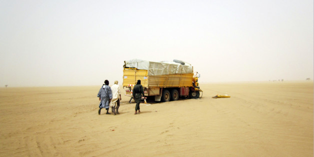 Militiaman from the Ansar Dine Islamic group approach a vehicle that had been involved in an accident in the desert of northeastern Mali, June 15, 2012. The U.N. Security Council on Monday declared its readiness to consider backing West African military intervention in Mali, where rebels and Islamist militants have seized control of much of the country, but said it needed more details on the plan. Picture taken June 15, 2012. REUTERS/Adama Diarra (MALI - Tags: POLITICS CIVIL UNREST CONFLICT RELI