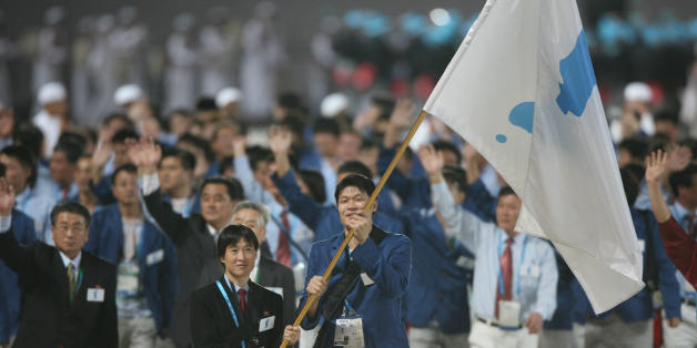 Doha, QATAR:  The Korean Unification flag is carried in front of the joint North and South Korean athletic delegation during the 15th Asian Games in Doha, 01 December 2006. After years of planning and billions of dollars in investment, the Asian Games officially opened in the Qatari capital Doha with what is being billed as the most spectacular gala ceremony ever seen, with more than 13,000 athletes from 39 countries angling for gold in 45 events.       AFP PHOTO / TOSHIFUMI KITAMURA  (Photo cre