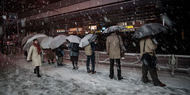 People wait in a queue for taxis at Akihabara station during a snowfall in Tokyo on January 22, 2018.Japan's weather agency issued a heavy snow warning for Tokyo for the first time in four years, urging people to go home early amid fears of public transport chaos. / AFP PHOTO / Behrouz MEHRI        (Photo credit should read BEHROUZ MEHRI/AFP/Getty Images)