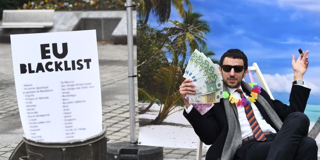 An Oxfam activist stages a satirical street-play mimicking a wealthy person hidding his money in a tax haven, on December 5, 2017 near the European institutions in Brussels, within a meeting of European Union ministers over a credible blacklist of non-EU tax havens. The EU has struggled for over a year to finalise the blacklist, with smaller, low-tax EU nations such as Ireland, Malta and Luxembourg worried about scaring off multinationals. / AFP PHOTO / EMMANUEL DUNAND        (Photo credit shoul