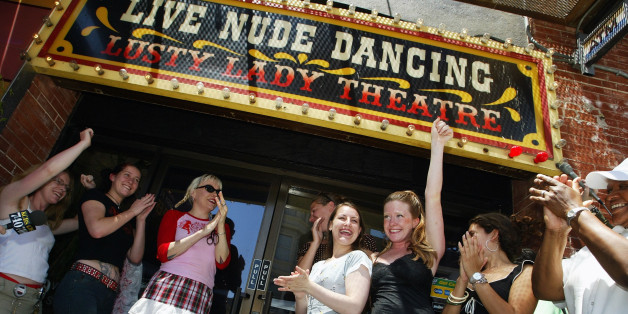 SAN FRANCISCO - JUNE 26:  Exotic dancers cheer after cutting a large garter belt to officially re-opening the Lusty Lady strip club June 26, 2003 in San Francisco.  The dancers and support staff of the Lusty Lady made history by saving the famous strip club from going out of business by becoming the first employee-owned, fully unionized strip club in the nation.  (Photo by Justin Sullivan/Getty Images)
