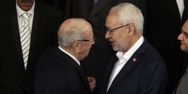Beji Caid Essebsi (L), leader of Tunisia's secular Nidaa Tounes party and a presidential candidate, shakes hands with Rached Ghannouchi, leader of the Islamist Ennahda movement, in the assembly building, in Tunis December 2, 2014. Tunisia's first full elected parliament held its opening session on Tuesday with a challenge to implement the democracy its people sought when they marched in the 2011 revolt against autocrat Zine el-Abidine Ben Ali. REUTERS/Zoubeir Souissi (TUNISIA - Tags: POLITICS EL