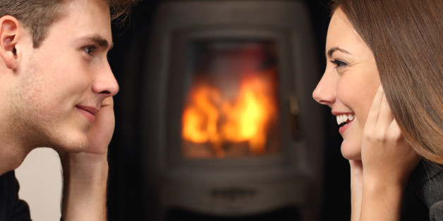 Side view of a couple flirting and looking each other in front a fireplace