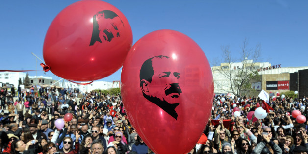 Tunisians release balloons bearing portraits of slain opposition leader Chokri Belaid outside his house in Tunis on March 17, 2013 as they mark 40 days since his killing. Belaid, a critic of the ruling Islamists whose death plunged Tunisia into turmoil, was gunned down outside his home on February 6 in a killing blamed by the authorities on radical Islamists, denying any involvement. Several arrests in the case have been made, but the suspected killer remains at large. AFP PHOTO / FETHI BELAID