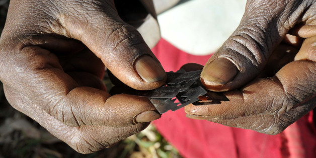 Prisca Korein, a 62-year-old traditional surgeon, holds razor blades before carrying out female genital mutilation on teenage girls from the Sebei tribe in Bukwa district, about 357 kms (214 miles) northeast of Kampala, December 15, 2008. The ceremony was to initiate the teenagers into womanhood according to Sebei traditional rites. REUTERS/James Akena (UGANDA)