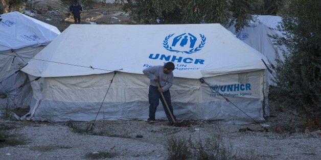 LESBOS, GREECE - NOVEMBER 21: A refugee digs with a shover in front of a United Nations High Commissioner for Refugees (UNHCR) Refugee Agency tent at the Moria Refugee Camp in Lesbos, Greece on November 21, 2017. Overpopulated refugee camp is comprised mostly of children and women.  (Photo by Ayhan Mehmet/Anadolu Agency/Getty Images)
