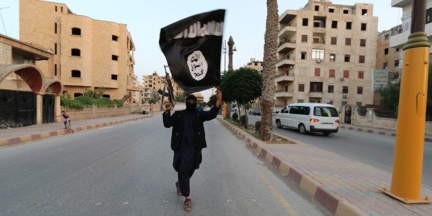 "A member loyal to the Islamic State in Iraq and the Levant (ISIL) waves an ISIL flag in Raqqa June 29, 2014. The offshoot of al Qaeda which has captured swathes of territory in Iraq and Syria has declared itself an Islamic ""Caliphate"" and called on factions worldwide to pledge their allegiance, a statement posted on jihadist websites said on Sunday. The group, previously known as the Islamic State in Iraq and the Levant (ISIL), also known as ISIS, has renamed itself ""Islamic State"" and proclaime"