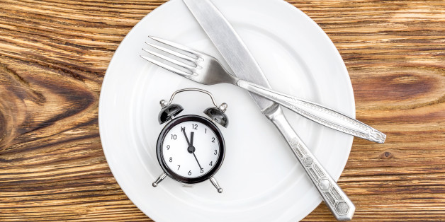 Alarm clock with fork, knife and plate on the table. Top view. Time to eat.