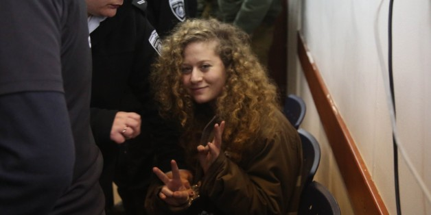 RAMALLAH, WEST BANK - FEBRUARY 13: Hanzala Courage Award winner 16-year-old Palestinian girl Ahed al-Tamimi who was detained by Israeli security forces last year, makes a victory sign as she arrives in court at Ofer Military Court in Ramallah, West Bank on February 13, 2018.  (Photo by Issam Rimawi/Anadolu Agency/Getty Images)